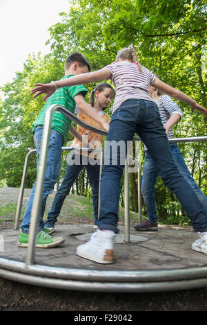 Kinder, die Spaß auf einem Karussell Spielplatz, München, Bayern, Deutschland - Stockfoto