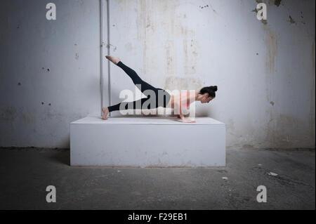 Mitte Erwachsene Frau üben Plank Pose auf Betonblock, München, Bayern, Deutschland - Stockfoto