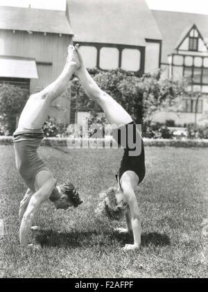 Seitenansicht des jungen Paares machen Handstand in Hof (OLVI008_OU348_F) - Stockfoto