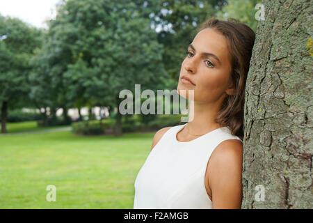 traurige junge Frau Baum gelehnt - Stockfoto