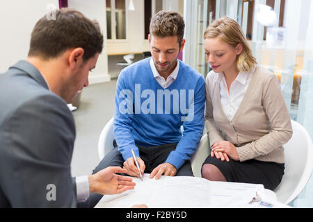 Paar Unterzeichnung Vertrag mit Finanzberater - Stockfoto