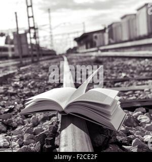 Nahaufnahme eines aufgeschlagenen Buches auf den Gleisen, in schwarz und weiß - Stockfoto
