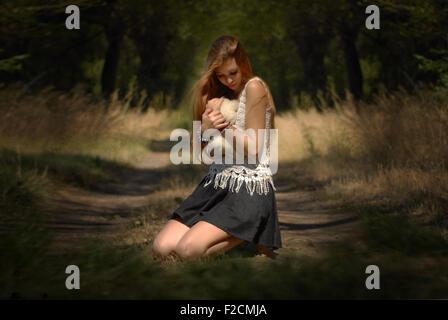Verlorene Seele und Unschuld - Mädchen umarmt Teddybär im Wald weinendes Mädchen im Wald mit Teddy Bär schönes Licht Stockfoto