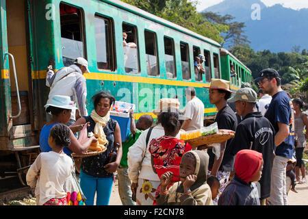 Verkäufer, die Lebensmittel auf Plattform des Bahnhofs zu Fluggästen Zug von Fianarantsoa nach Manakara, Madagaskar - Stockfoto