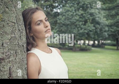 traurige junge Frau lehnte sich gegen Baum-retro-Stil - Stockfoto