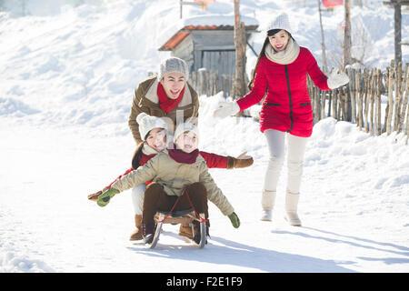 Glückliche Familie mit Schlitten im Schnee spielen - Stockfoto