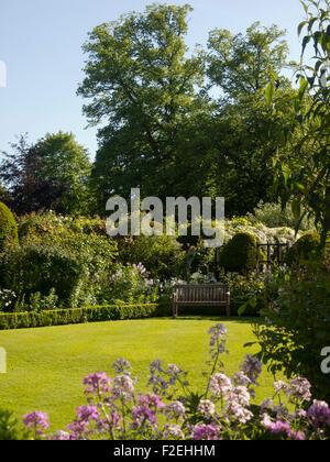 Porträt auf Chenies Manor Rasen; eine Ecke mit Gartenbank, Buchsbaumhecken, Statue, rosa süß Rakete Grenze und blauer - Stockfoto
