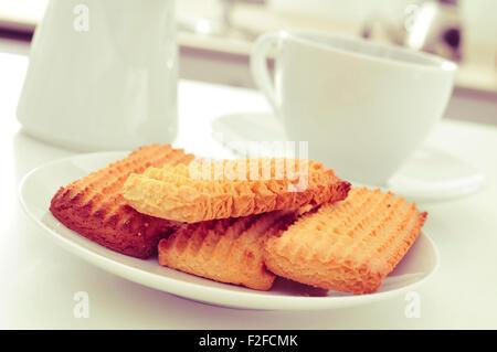 Nahaufnahme einer Platte mit einem Haufen von hausgemachten Keksen und einer Tasse Kaffee oder Tee auf dem Küchentisch