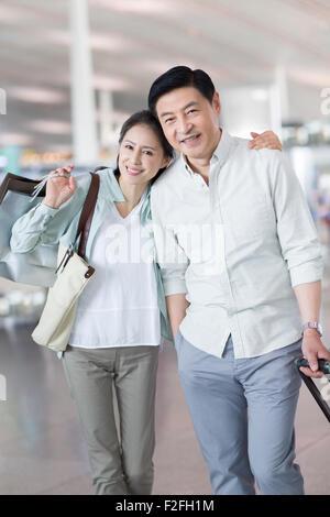 Älteres Paar warten am Flughafen mit Einkaufstüten - Stockfoto