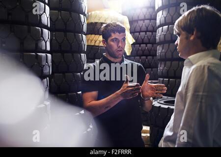 Mechaniker und Kunden sprechen in der Nähe von gestapelten Reifen - Stockfoto