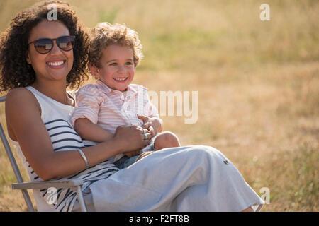 Porträt, Lächeln, Mutter und Sohn im sonnigen Feld - Stockfoto