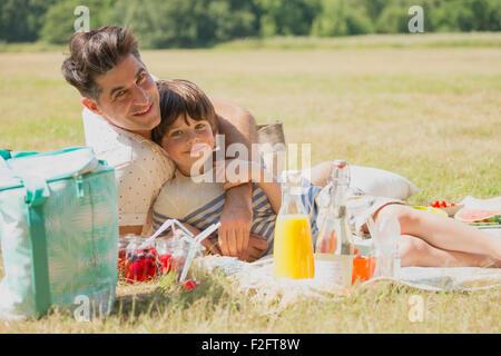 Porträt liebevoller Vater und Sohn auf der Picknickdecke im sonnigen Bereich entspannend - Stockfoto