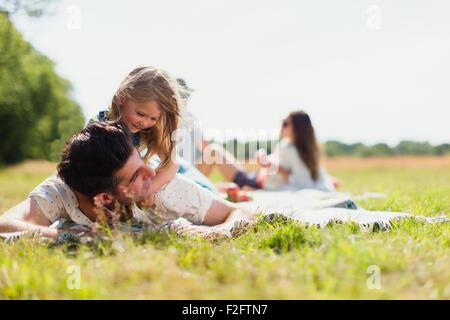 Liebevolle Tochter Verlegung auf Vaters im sonnigen Bereich - Stockfoto