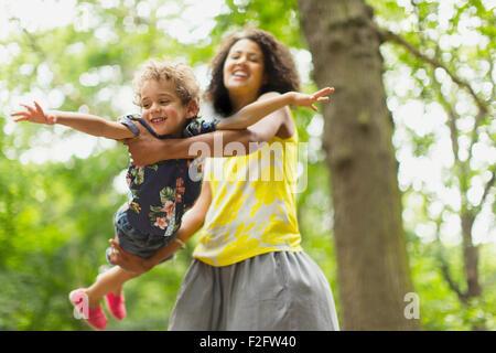 Spielerische Mutter fliegenden Sohn unter Baum - Stockfoto