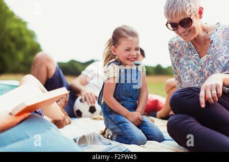 Großmutter und Enkelin lachend auf Decke - Stockfoto