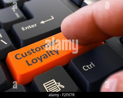 Einem Finger Pressen orangen Button Kundenbindung auf schwarzen Computertastatur. Detailansicht. Selektiven Fokus. - Stockfoto