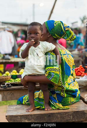 Benin, Westafrika, Porto-Novo, Kind mit seiner Mutter in einem Markt eine Banane essen - Stockfoto