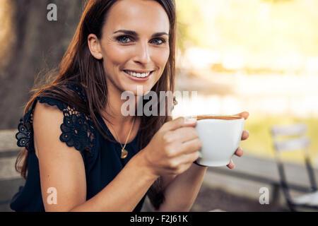 Porträt der lächelnde junge Frau mit einer Tasse Kaffee in der hand Blick in die Kamera während im Café. - Stockfoto