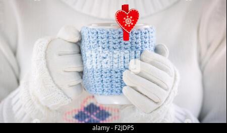 Gestrickter Wolle-Cup in Menschenhand. Mit roten Herzen. - Stockfoto