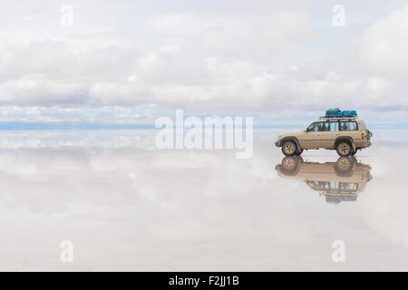 Offroad-Fahrzeug auf die reflektierte Oberfläche des Sees Salar de Uyuni in Bolivien - Stockfoto