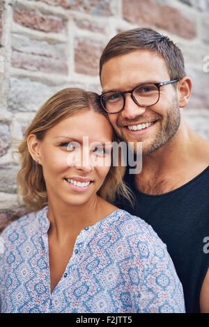 Junge süße paar schaut in die Kamera mit Toothy Lächeln hautnah. - Stockfoto
