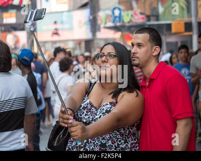 Ein junges Paar nimmt ein Selbstporträt mit einem Selfie-Stick während der Times Square in New York City zu besuchen. - Stockfoto