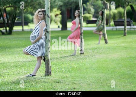 Drei junge Schwangere ihren Bauch halten und lehnt sich an einem kleinen Baum im Park. - Stockfoto