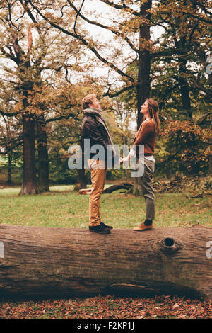 Junges Paar in Liebe Hand in Hand auf einem Baumstamm in einem herbstlichen park - Stockfoto