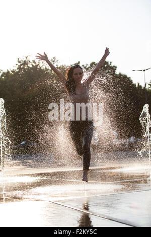 Frau rennt durch Brunnen Plätschern Wassertropfen - Stockfoto