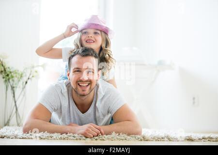 Vater und Tochter auf Boden liegend, Mädchen spielen mit Hut - Stockfoto