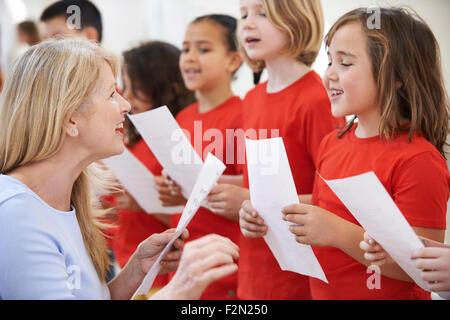 Kinder In Gesangsgruppe gefördert durch Lehrer - Stockfoto