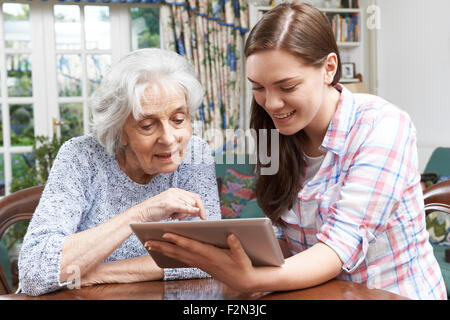 Teenager Enkelin zeigt Großmutter wie Nutzung Digital-Tablette - Stockfoto