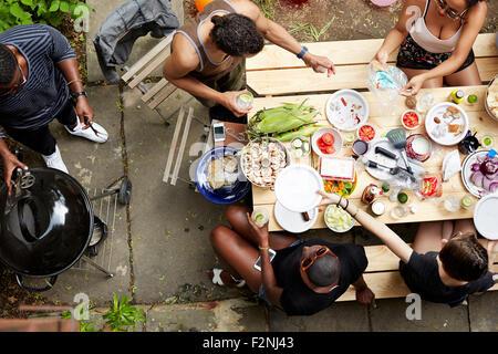 Erhöhte Ansicht von Freunden Essen im Hinterhof Grill Stockfoto