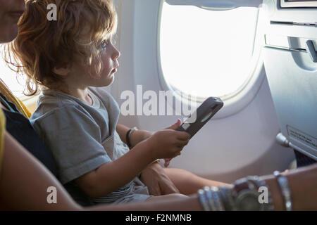 Kaukasische Mutter und Baby Sohn mit Handy im Flugzeug - Stockfoto