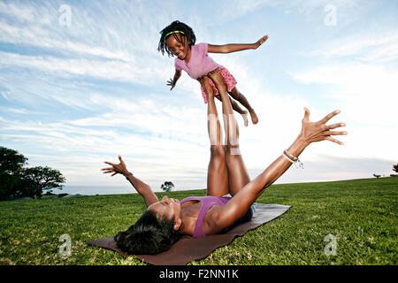 Mutter ausgleichende Tochter auf Beinen im park - Stockfoto