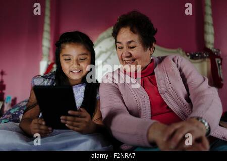 Hispanische Großmutter und Enkelin mit digital-Tablette auf Bett - Stockfoto
