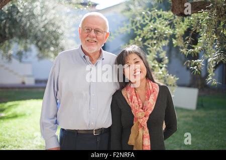 Älteres Ehepaar lächelnd in Hinterhof - Stockfoto