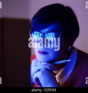 Nachdenklich Geschäftsfrau mit Computer-Bildschirm spiegelt sich in ihrer Brille - Stockfoto