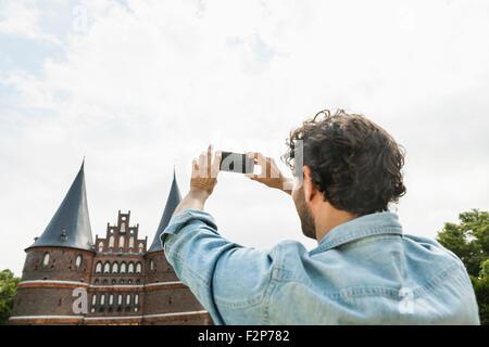 Deutschland, Lübeck, Mann unter Bild vor dem Holstentor - Stockfoto