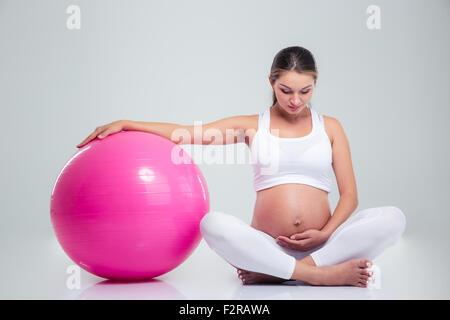 Porträt einer schönen schwangeren Frau sitzen auf dem Boden mit Fitness-Ball auf einem weißen Hintergrund isoliert - Stockfoto