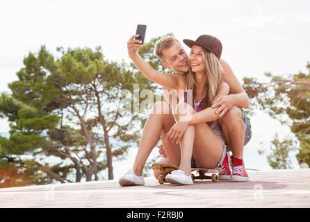 Brautpaar mit sitzen im Freien auf Skateboard und nehmen ein Selbstporträt - Stockfoto