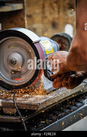 mA-Hufschmied bei der Arbeit ein Hufeisen auf einer Maschine mit Funken Re-shaping. - Stockfoto