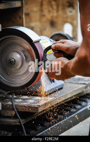 Ein Hufschmied bei der Arbeit ein Hufeisen auf einer Maschine mit Funken Re-shaping. - Stockfoto