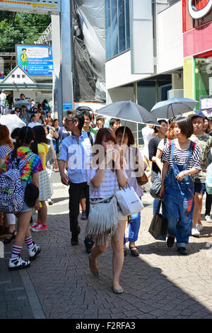 Zu Fuß Mädchen in der Öffentlichkeit Essen. Harajuku, Tokio. - Stockfoto