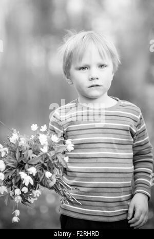 Kleiner Junge mit Waldblumen (Anemone) - Stockfoto