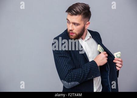 Porträt eines Geschäftsmannes, Geld in Jacke und wegsehen auf grauem Hintergrund - Stockfoto