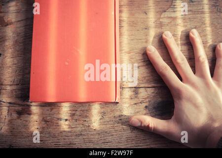 Hand und auf einem Tisch mit Schatten von Jalousien - Stockfoto