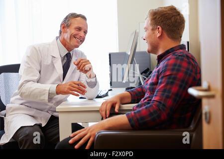 Patienten mit Beratung mit männlichen Arzt In Büro - Stockfoto