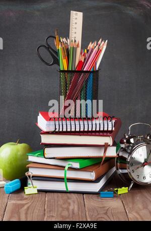 Schul- und Büromaterial auf Klassenzimmer Tisch vor Tafel - Stockfoto
