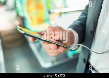 Mann mit Handy Musik zu hören. am Bus. SMS-Nachricht. Close-up Hände - Stockfoto